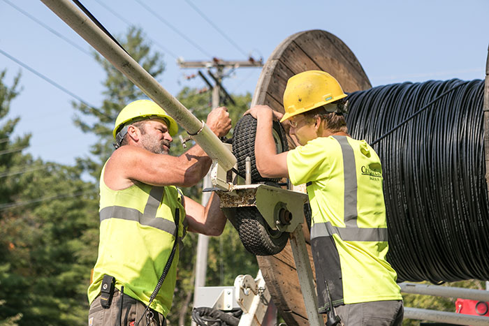 central cable workers unrolling a cable spool