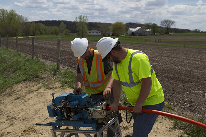central cable workers cutting tubing
